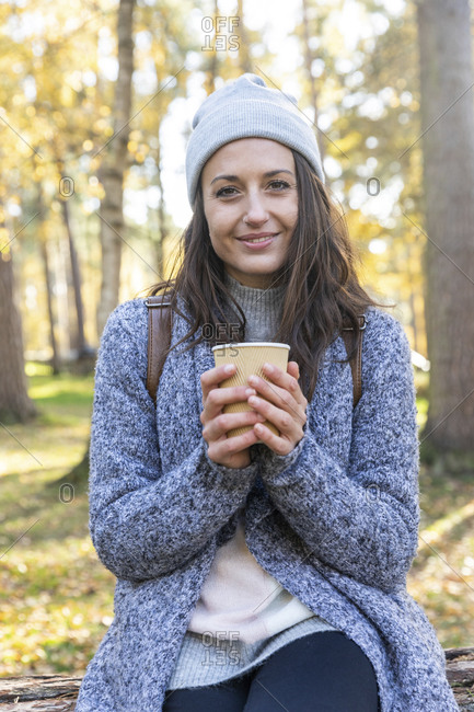 Smiling female hiker holding tea cup in Cannock Chase woodland during winter