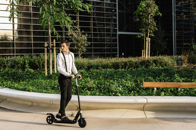 Businessman on electric push scooter in city
