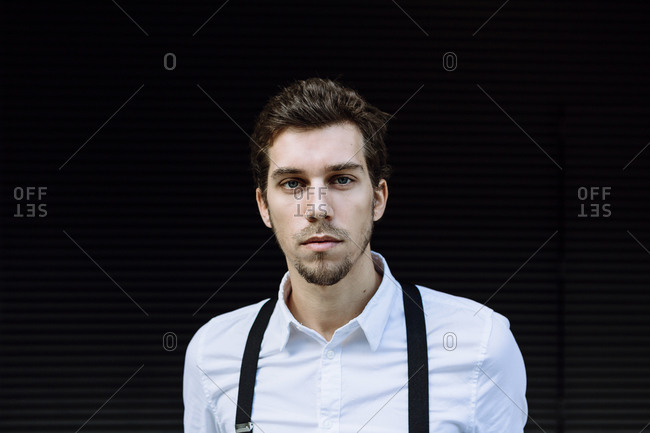 Portrait of stylish businessman wearing white shirt and black suspenders