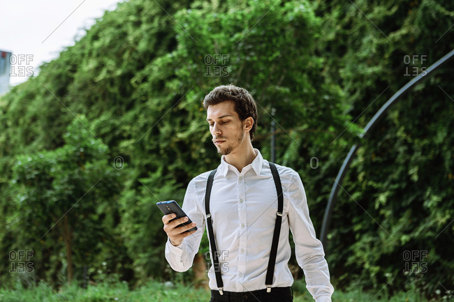 Businessman wearing white shirt and black suspenders looking at smart phone outdoors