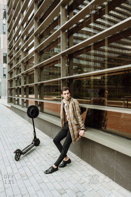 Stylish man in check jacket with push scooter sitting at modern building in city