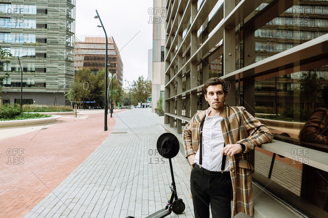 Portrait of stylish man in check jacket with push scooter standing at modern building in city