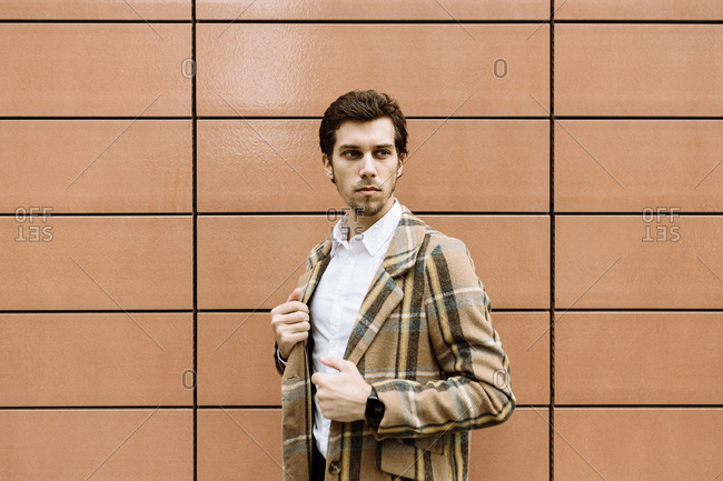 Portrait of stylish man in check jacket in city