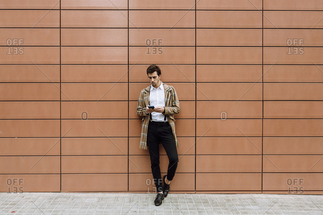 Stylish man in check jacket leaning against wall and using smart phone
