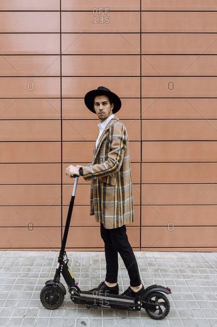 Stylish young man wearing checked jacket and hat standing with push scooter in city