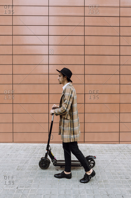 Stylish young man wearing checked jacket and hat walking with push scooter in city