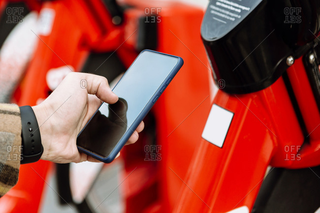 Mans hand holding smart phone to rent bicycle