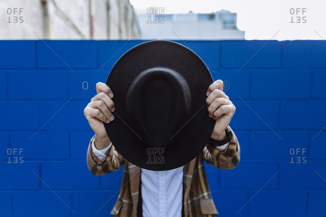 Stylish man wearing checked jacket holding black hat in front of face against blue wall