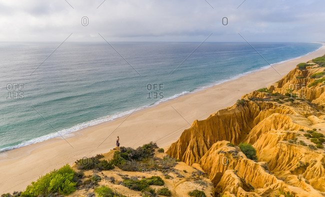 Aerial view of woman standing on side of cliff overlooking long beach in Portugal.