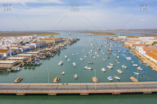 September 13, 2020: Aerial view of a harbor with the boats docked and a bridge over the Rio Carrera connecting the island of Isla Cristina, Huelva, Spain.