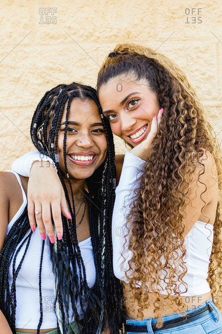 Portrait of beautiful multiracial women hugging and smiling with a yellow wall