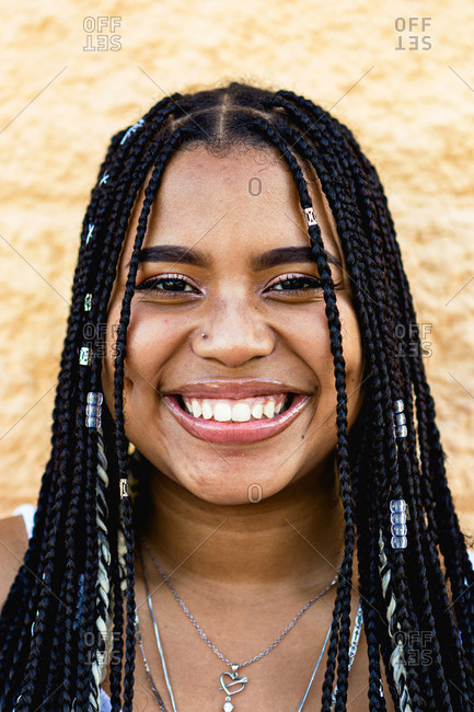 Portrait of a beautiful black woman with braids smiling with a yellow wall