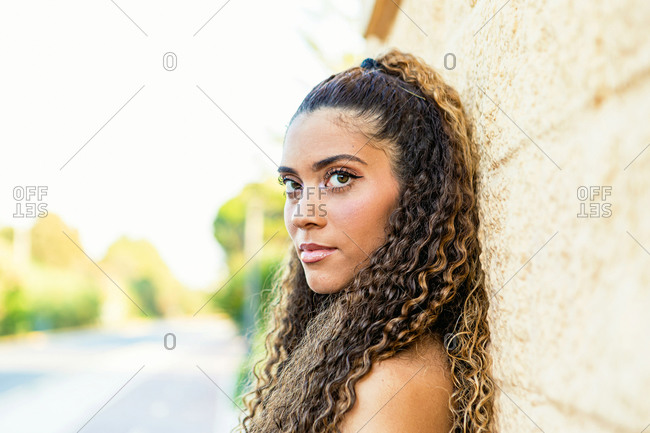 Portrait of a beautiful Latin woman with curly hair leaning on the wall on the street