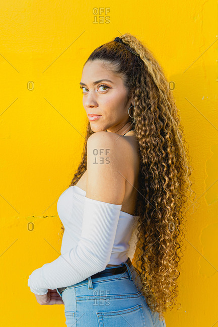 Portrait of a beautiful Latin woman with curly hair leaning on a yellow wall