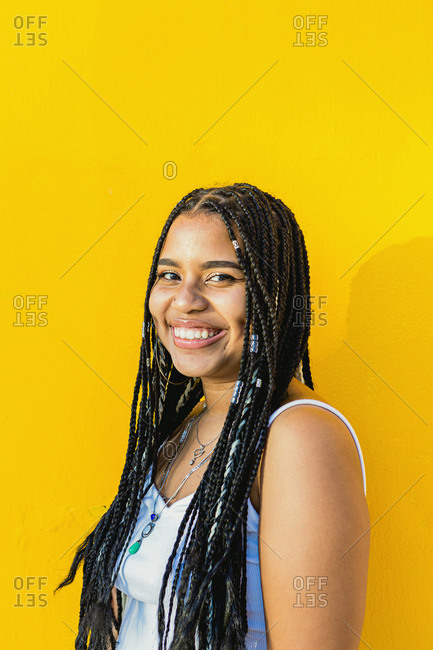 Portrait of a beautiful black woman with braids smiling with a yellow background