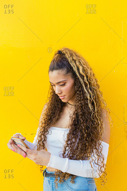 Portrait of a beautiful Latin woman with curly hair using her phone with a yellow background