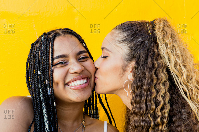 Portrait of a beautiful Latin woman kissing a black woman with braids with a yellow background