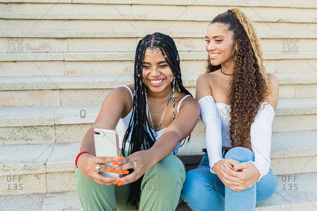Portrait of a beautiful multiracial women taking a selfie sitting on the street stairs