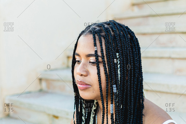 Portrait of a beautiful black woman with braids sitting on the street stairs