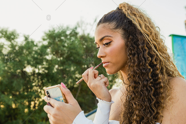Portrait of a beautiful Latin woman with curly hair putting on lip makeup on the street