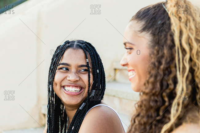 Portrait of a beautiful black woman with braids smiling to a Latin woman