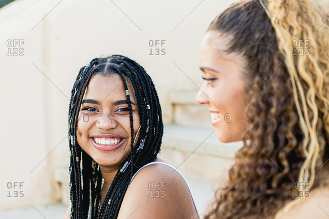 Portrait of a beautiful black woman with braids smiling and looking at camera next to a Latin woman