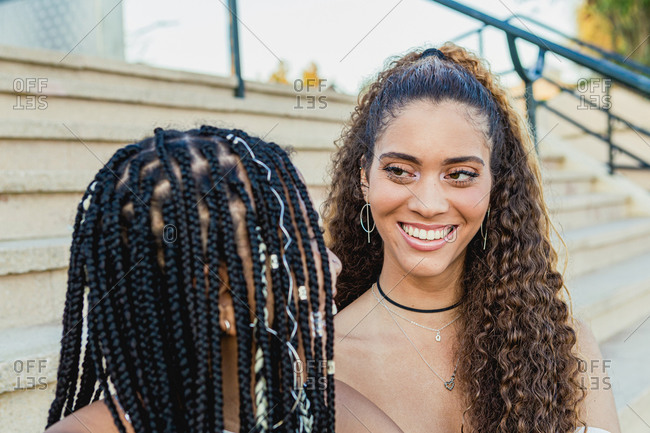 Portrait of a beautiful Latin woman with curly hair smiling to a black woman