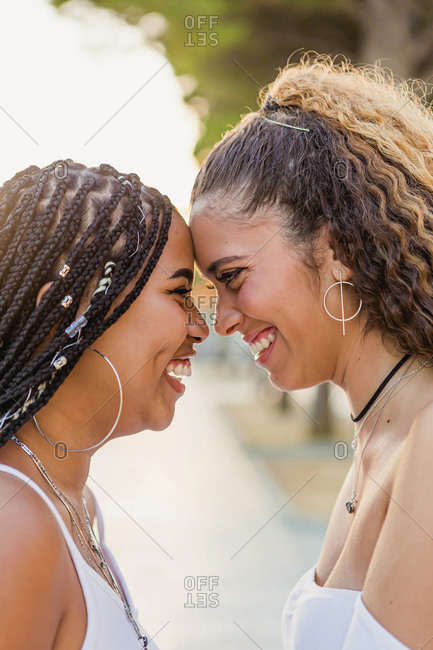 Portrait of a beautiful multiracial woman laughing and looking at each other on the street with the sunset behind her