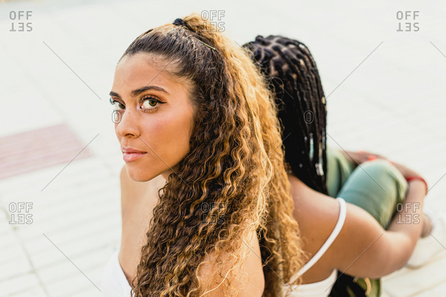 Portrait of a beautiful Latin woman looking at the camera leaning on the back of a black woman in the street