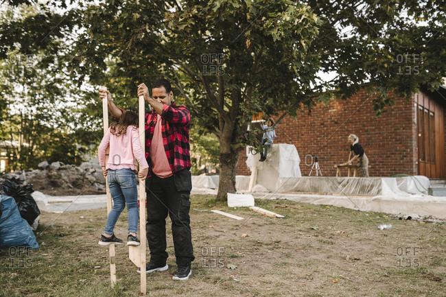 Father helping daughter balance on wooden sticks in yard