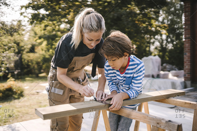 Mother measuring wooden plank by son at construction site
