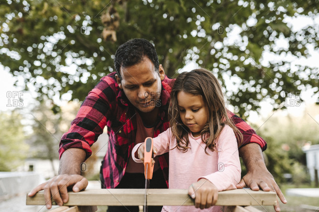 Girl cutting wooden plank by father during summer