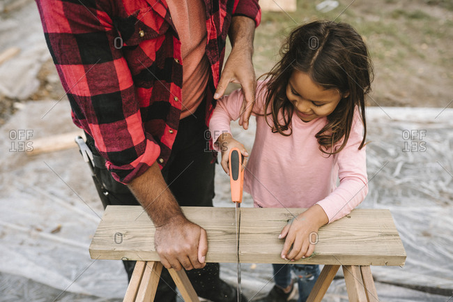 High angle view of smiling girl cutting wooden plank by father during summer