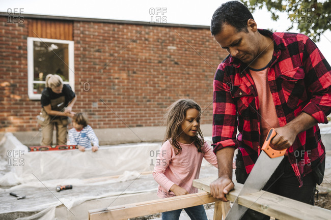 Father and daughter using hand saw while mother with son by concrete wall against house