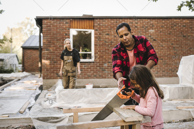Daughter using hand saw by father while mother standing by concrete against house