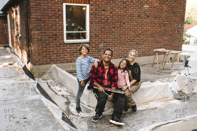 Portrait of smiling couple and children sitting on concrete wall against house