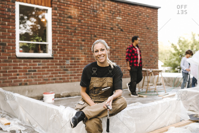 Portrait of smiling mother sitting on concrete while family working in background during summer