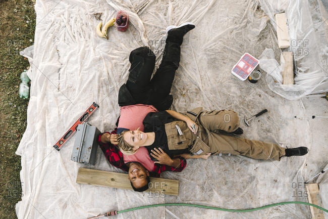 High angle view of smiling woman resting on partner after renovating during summer