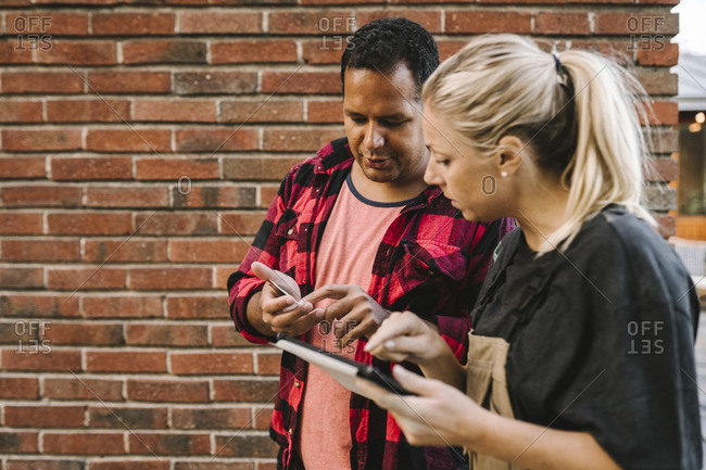 Contemplating man talking to female partner with digital tablet against brick wall
