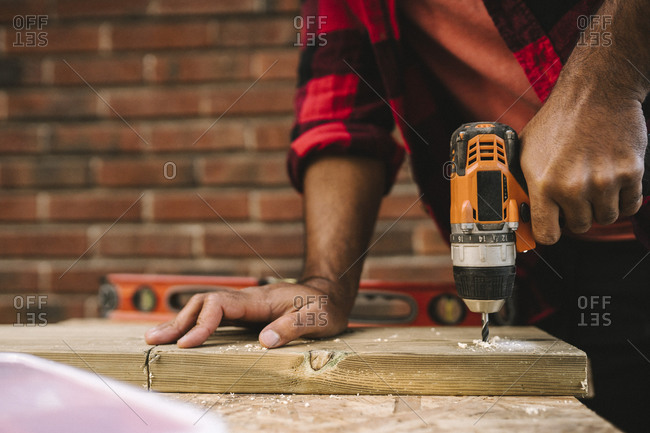 Midsection of man using drill machine on plank while renovating during summer