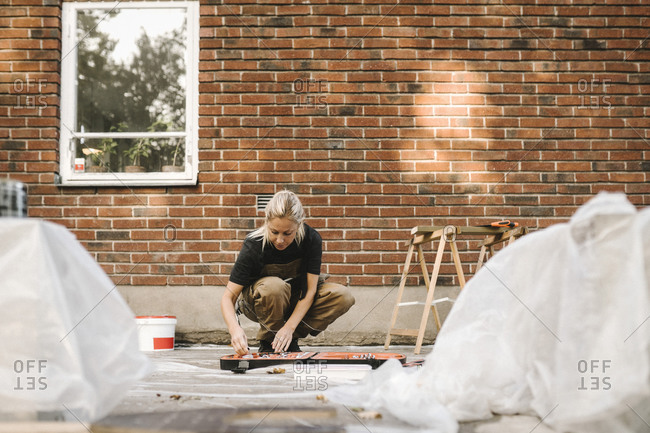 Woman crouching while renovating house during summer