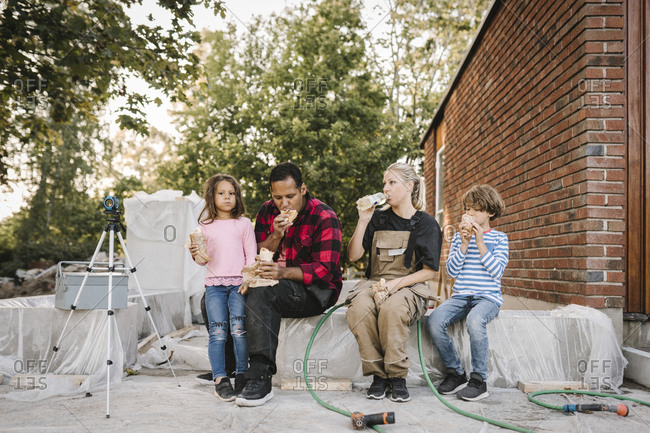 Tired parents with children eating food while sitting on concrete block against house