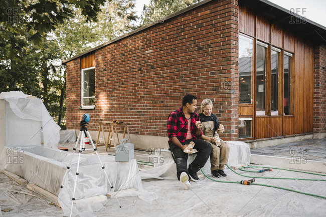 Heterosexual couple eating food while resting on concrete block against house
