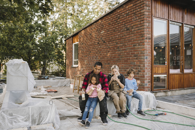 Tired parents with children eating food while resting on concrete block against house
