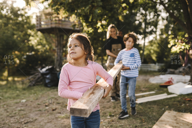 Confident girl with family carrying wooden plank in yard