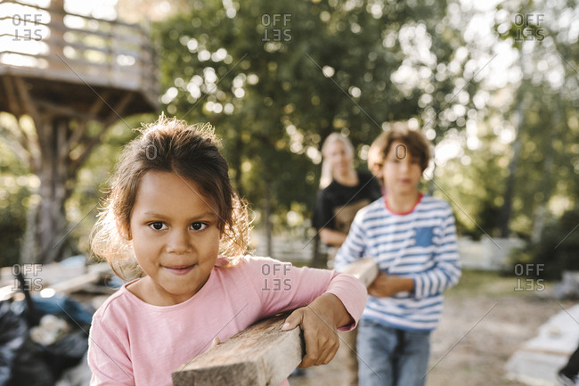 Smiling girl with brother and mother carrying wooden plank in yard