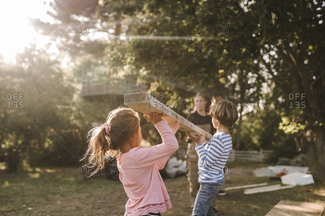 Parents and children carrying wooden plank in yard