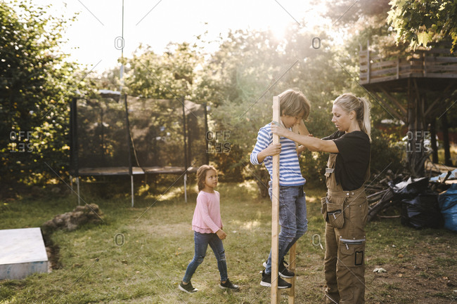 Side view of mother helping son stand on wooden supporter while daughter looking in yard
