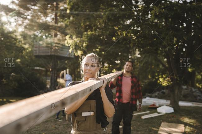 Heterosexual couple carrying wooden plank in backyard