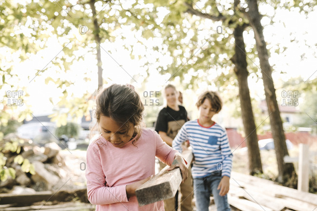 Smiling girl with family carrying wooden plank in yard